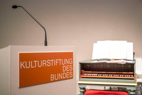 """Rednerpult mit der Aufschrift """"Kulturstiftung des Bundes"""", dahinter ein Tasteninstrument"""
