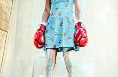 Frau mit roten Boxerhandschuhen, steht aufrecht und schaut entschlossen