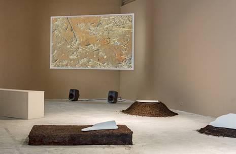 Sandfarbener Ausstellungsraum mit einem Bildschirm und Lautsprechern im Zentrum, auf dem Boden davor Erdhaufen