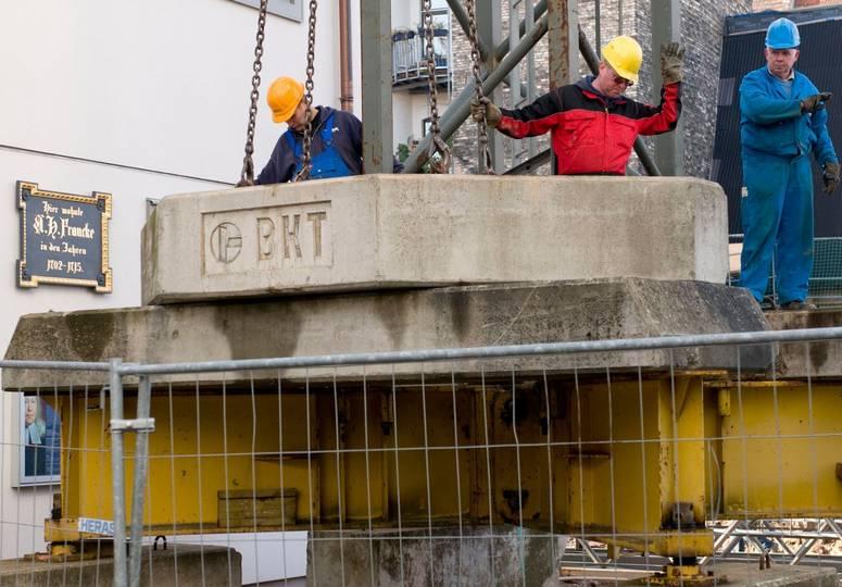 Drei Bauarbeiter um eine Betonplatte, die in die Luft gehoben wird