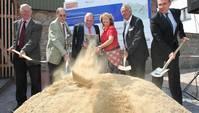Fünf Männer und eine Frau mit Spaten in den Händen hinter einem großen Sandhügel