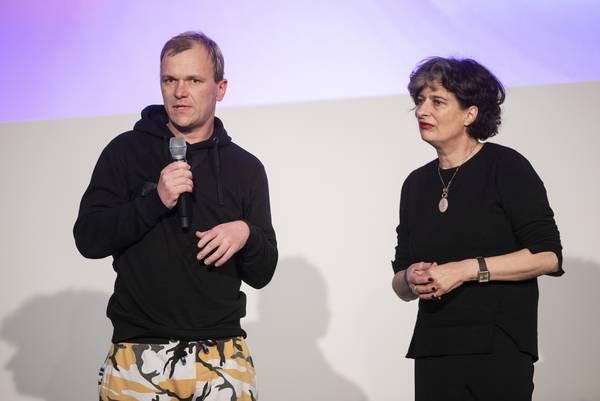 zwei stehende Personen: links Mann mit Mikrofon in der Hand, rechts Frau
